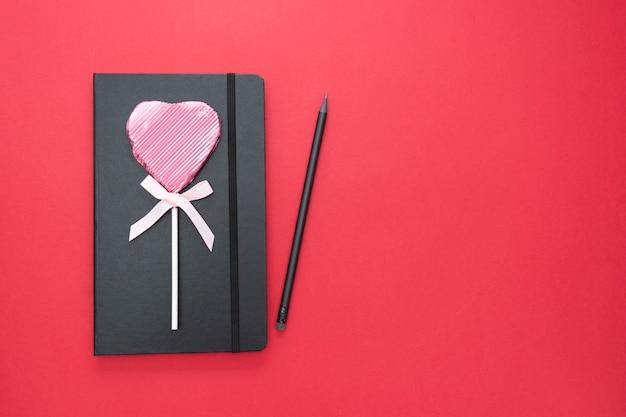 バレンタインデーのテンプレート。ハート型のロリポップとコピースペースと赤の背景に黒のノートブック。 Premium写真