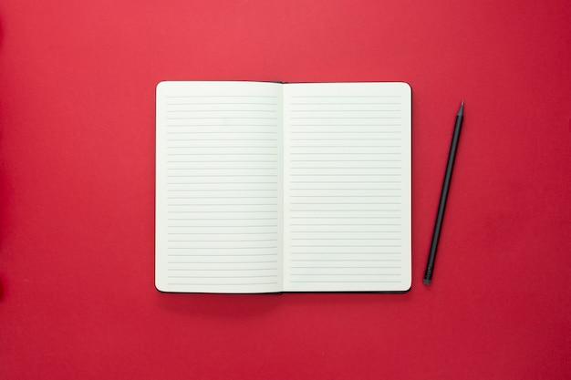 赤い背景に分離されたノートブックを開く、テキスト用のスペースをコピーします。 Premium写真