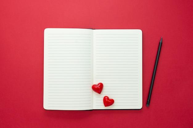 バレンタイン・デー。赤いハートと赤い背景の上の鉛筆でノートブックを開き、テキスト用のスペースをコピーします。 Premium写真