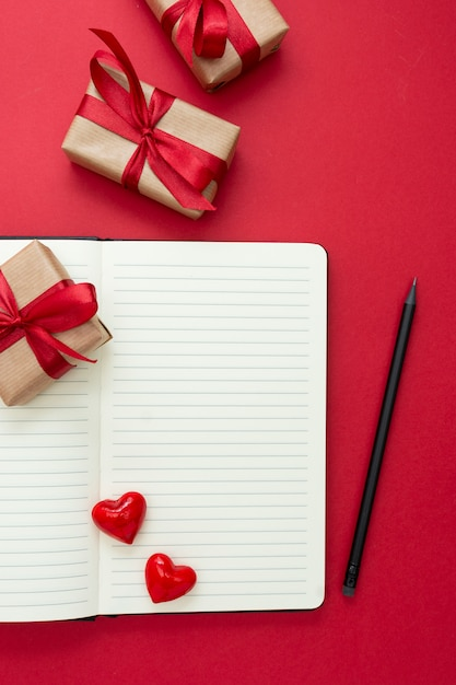 バレンタインデーのモックアップ。赤いハートと赤い背景のギフトボックスでノートブックを開くには、テキスト用のスペースをコピーします。 Premium写真