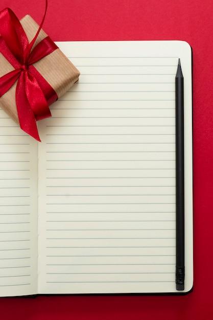 バレンタインデーのモックアップ。赤い背景の上のギフトボクセでノートブックを開く、テキスト用のスペースをコピーします。 Premium写真