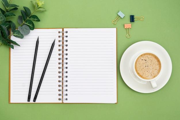 空のページとコーヒーカップでノートブックを開きます。テーブルトップ、緑の背景の作業スペース。創造的なフラットレイアウト。 Premium写真