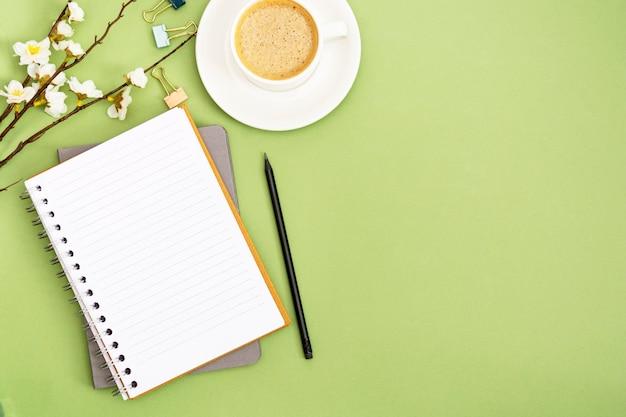 空のページとコーヒーカップでノートブックを開きます。春のテーブルトップ、緑の背景の作業スペース。創造的なフラットレイアウト。 Premium写真