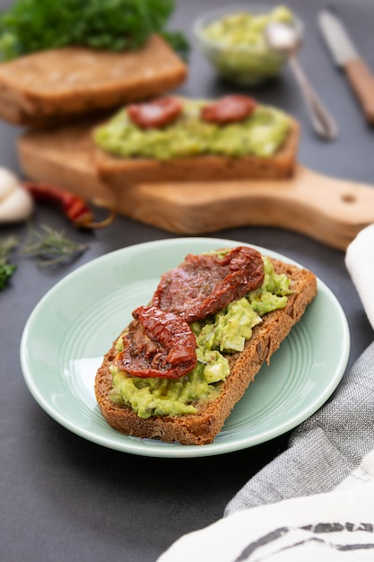 Здоровая пища. ржаной хлеб с гуакомоле, пастой из авокадо и вялеными томатами, на деревянной разделочной доске. авокадо тост. Premium Фотографии