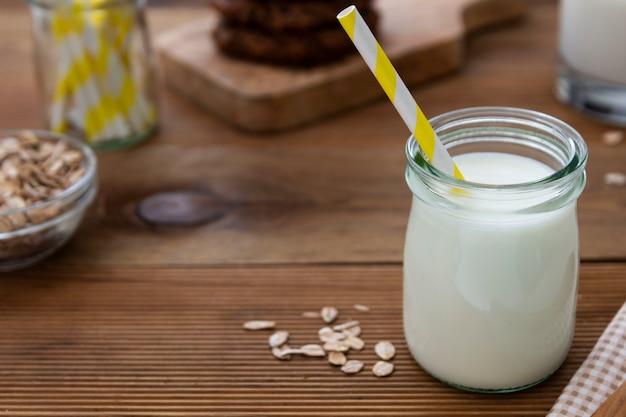 ガラスの瓶、木製の背景に紙ストローでオート麦ミルクのボトル Premium写真