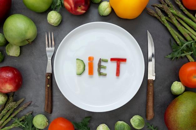 Концепция диеты. круглая тарелка со словом - диета - состоит из кусочков разных фруктов и овощей Premium Фотографии