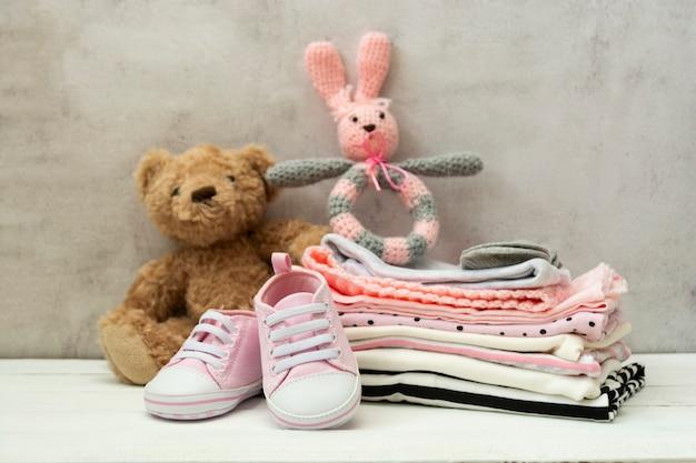 Розовая детская обувь, одежда для новорожденных и мягкие игрушки. концепция материнства, образования или беременности с космосом экземпляра. Premium Фотографии