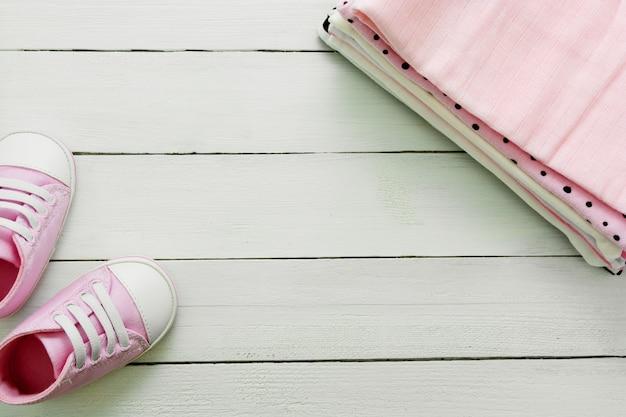 Розовая детская обувь и новорожденная одежда. концепция материнства, образования или беременности с космосом экземпляра. плоская планировка Premium Фотографии