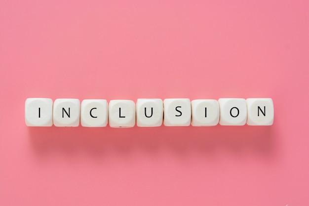 Текст включения сделанный от деревянных кубиков на розовой таблице. инклюзивная социальная концепция. квартира лежала. Premium Фотографии