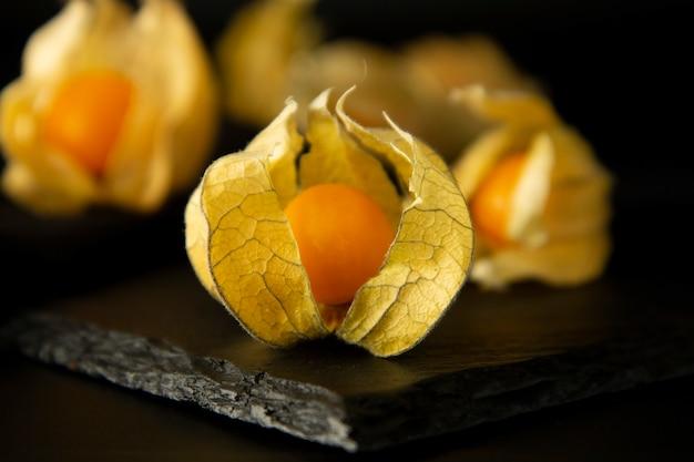 サイサリスの花、黒の背景に分離されたフルーツ。 Premium写真