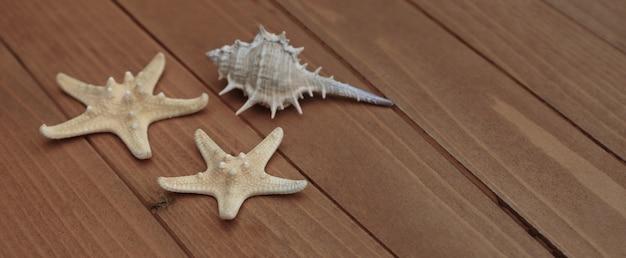 ヒトデと貝殻。茶色の木製の背景上の海事航海装飾 Premium写真