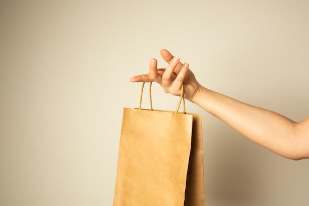 Крупный план женской руки держа пакет бумаги ремесла, насмешка дизайна вверх. концепция нулевой пасхи. Premium Фотографии