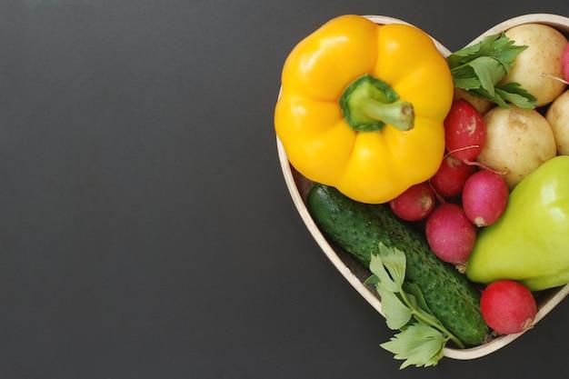 Здоровые натуральные продукты, овощи в деревянной коробке формы сердца. Premium Фотографии