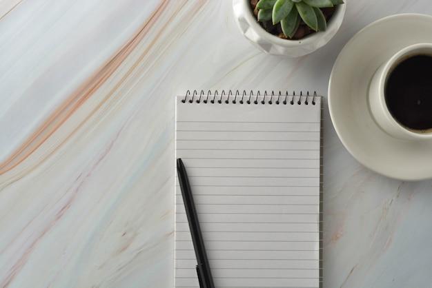 一杯のコーヒー、大理石の机の上の多肉植物でノートブックを開く。職場、作業テーブル上面図。 Premium写真