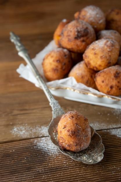 テーブルの上の小さな自家製ドーナツのクローズアップ。甘いデザートチーズの丸いドーナツ。 Premium写真
