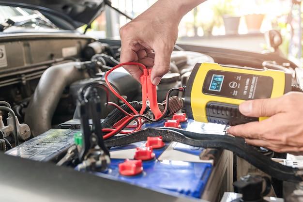 自動車整備士は電圧測定器を使用し、バッテリーを充電しています Premium写真