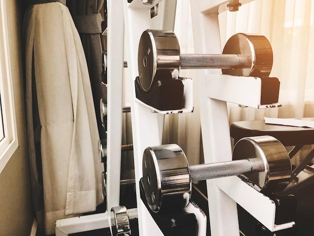 ダンベルのクローズアップグループは、ジムで腕の筋肉を行使するためのさまざまな重み。 Premium写真