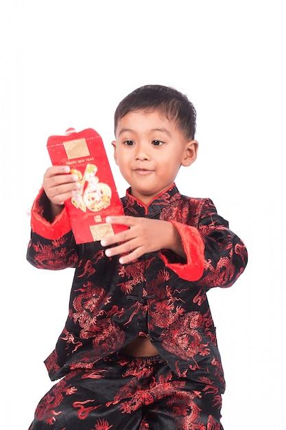 幸せな中国の旧正月、赤い封筒を保持しているアジアの小さな男の子 Premium写真