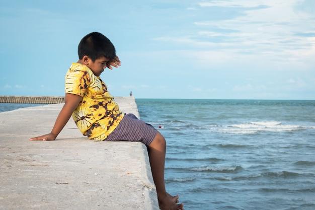 海の通路に一人で座っているかわいい男の子 Premium写真