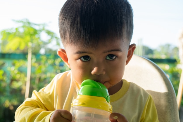 かわいい男の子のボトルから水を吸う Premium写真