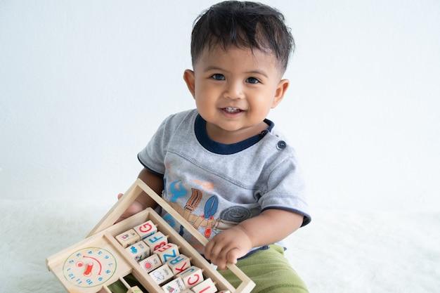 Милый маленький мальчик асин играет с деревянной игрушкой Premium Фотографии