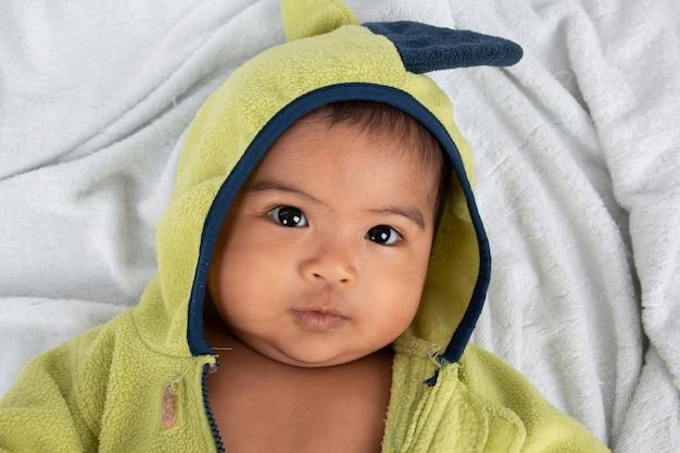柔らかい毛布と笑顔の上に横たわる幸せな小さな男の子 Premium写真