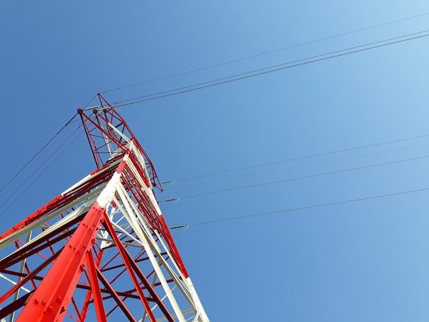 高電圧の塔の詳細は、山の上に赤を描いた。 Premium写真