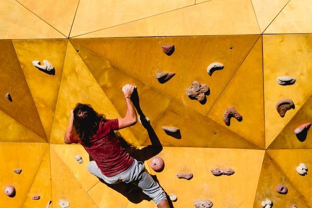 屋外クライミングウォールで太陽への複雑なルートをしようとしている男性のクライマー Premium写真
