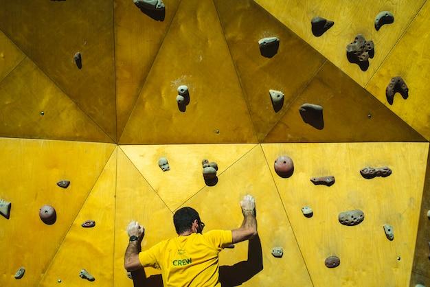 彼の手と足の強さでクライミングウォールの頂点に到達しようとしている運動選手男 Premium写真