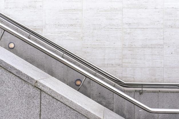 Стальные поручни на гранитных лестницах с фоном стены. Premium Фотографии