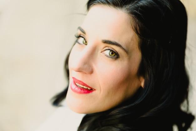 長いブルネットの髪とカメラ、ファッションの肖像画を見て緑の目を持つ美しい女性。 Premium写真