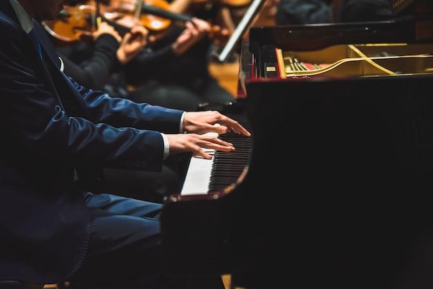 ピアニストがコンサートでグランドピアノで曲を弾いて、側面から見た。 Premium写真