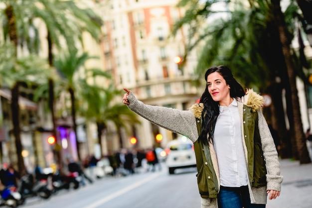 Женщина средних лет приветствует такси с поднятой рукой на улице. Premium Фотографии