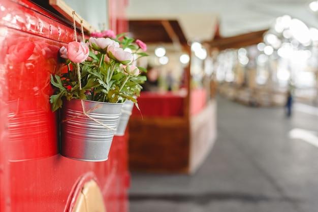 Горшки с декоративных растений, висит от красного автобуса на выставке старинных автомобилей. Premium Фотографии