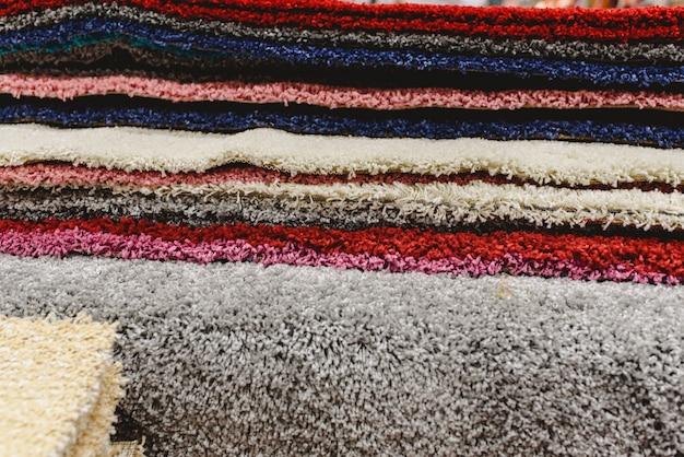 さまざまな色のカーペットが倉庫に積み上げられています。 Premium写真