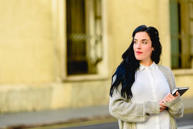 彼女の本とノートを彼女の手で歩いている成熟した学生女性。 Premium写真