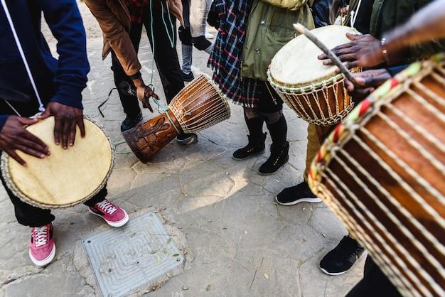 アフリカのドラマーが路上でボンゴを吹いています。 Premium写真