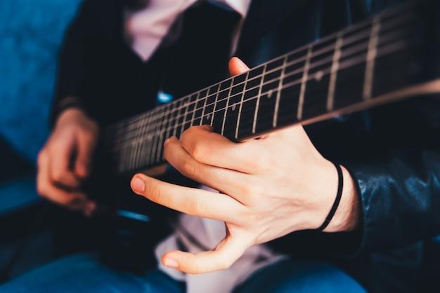 エレキギターで和音を弾くギタリストの指の詳細。 Premium写真
