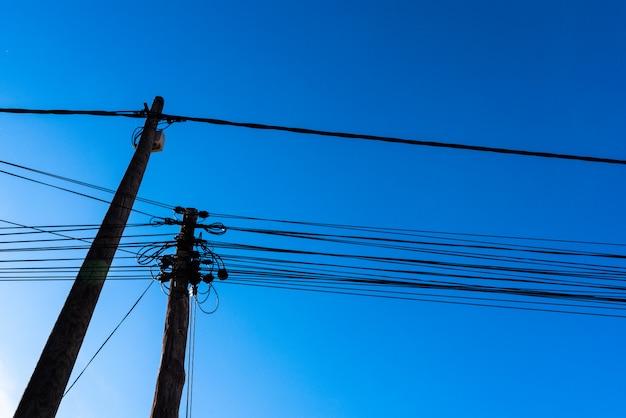 青い空を背景に下から見た電気通信ケーブル付きのポール。 Premium写真