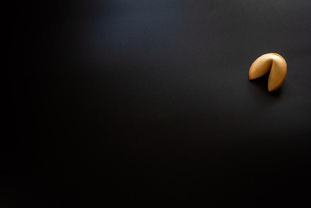 黒い背景にフォーチュンクッキー。 Premium写真