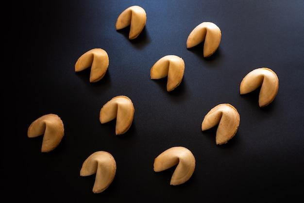 対称的に配置された暗い背景上のフォーチュンクッキー Premium写真