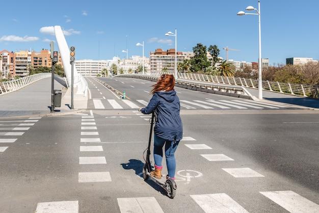 バレンシア市内の自転車道に車なしで通りを横切る電動スクーターの女性。 Premium写真