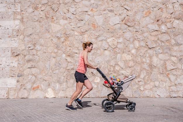 Женщина, мать делает фитнес, толкая коляску. Premium Фотографии