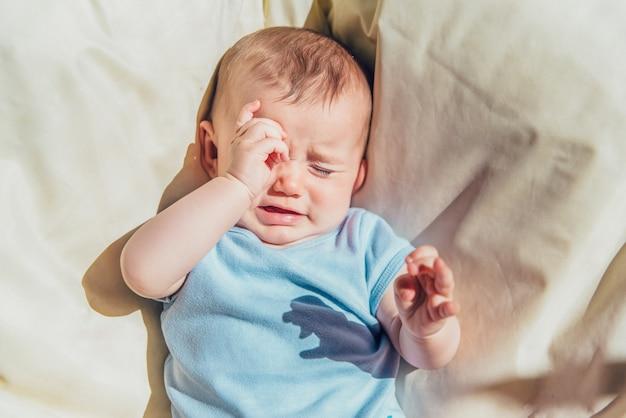 赤ちゃんは怒っていると、両親を呼んで泣いている太陽の下で横になります。 Premium写真