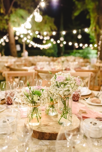 結婚式場のテーブルの上の豪華なカトラリーでセンターピースを飾る花。 Premium写真