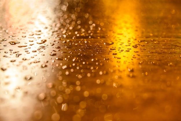 街灯で一晩照らされた木製のテーブルの上の雨の滴。 Premium写真