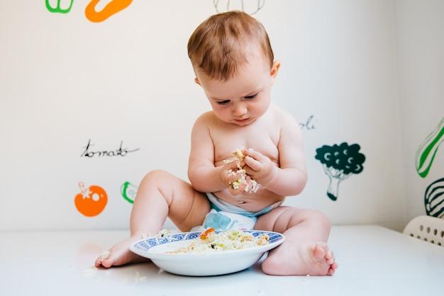 赤ちゃんは一握りの食べ物を口に入れて食べます。 Premium写真