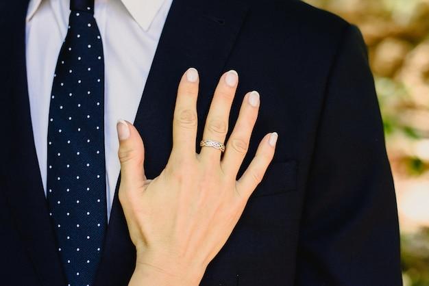 愛の女は、エレガントなスーツを着た彼の男の胸に彼女の手を傾けています。 Premium写真
