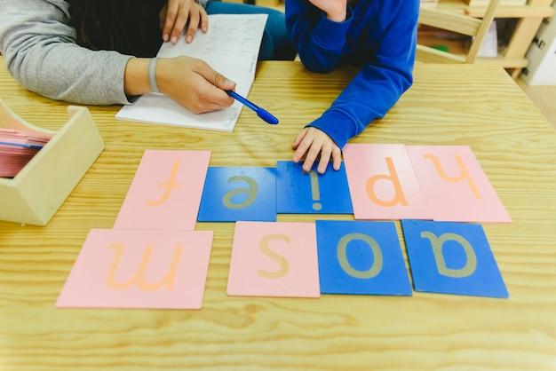 モンテッソーリ学校で識字の分野で書くことを学ぶ子供たち。 Premium写真