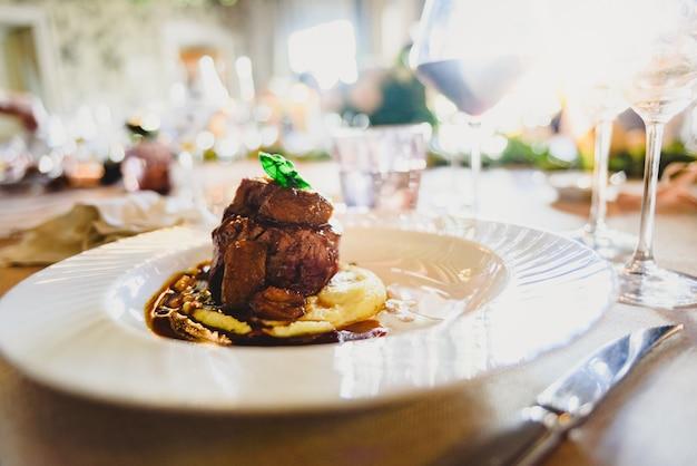 肉料理は、イベントレストランでの豪華な結婚式で優雅にお召し上がりいただけます。 Premium写真